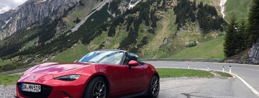 ein roter Mazda MX 5 ND der vor einer bergkette steht