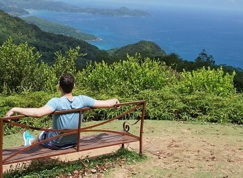Mann auf Bank der ein Berg Meer panorama betrachtet