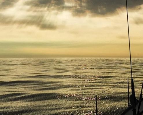 Blick von einem Segelboot auf das offene Meer. Der Himmel ist mit Wolken bedeckt und die Sonne scheint warmweiß durch sie hindurch.