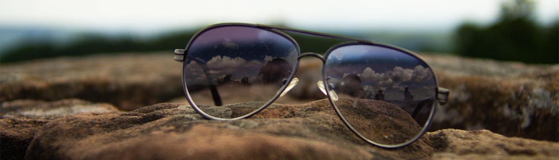 Sonnenbrille in Nahaufnahme auf einer alten Mauer. Titelbild des Blogbeitrages Wie Inflation deine Sparanstrengungen negativ beeinflusst.