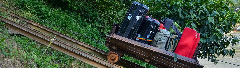 Koffer die auf einer Bahnschiene den Berg hinauf gefahren werden. Konsumkredit abgeschlossen